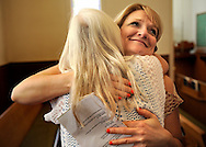 "13 MAY 2012 -- FESTUS, Mo. -- Cindy Kannady (right) embraces Sandra Danback as worshipers share the peace, saying to one another that ""the peace of God is with you,"" during the final church service at the First Presbyterian Church in Festus Sunday, May 13, 2012. The congregation is merging with nearby Grace Presbyterian Church in neighboring Crystal City. Photo © copyright 2012 Sid Hastings."