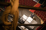 Fulvio Michelazzi, stage designer, takes down the backdrop of the scenary after the last play of Les mains sales (The dirty hands) by Jean Paul Sartre at Oscar theatre in Milan, Aprile 25, 2010. In the background the stalls of the theatre.