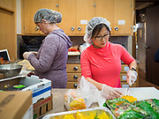 """26 FEBRUARY 2020 - FARMINGTON, MINNESOTA: ALIA TOBIN, right, and MARY SUE BRIGGS, both from Farmington, volunteers at the community dinner at Faith Church, work in the kitchen before the dinner. Faith Church is a United Methodist Church in Farmington, MN, about 30 minutes south of the Twin Cities. The dinner is sponsored by Loaves & Fishes, a Christian organization that provides food for community dinners and foodbanks. Farmington, with a population of 21,000, is a farming community that has become a Twin Cities suburb. The city lost its only grocery store, a Family Fresh Market, in December, 2019. The closing turned the town into a """"food desert."""" In January, Faith Church started serving the weekly meals as a response to the store's closing. About 125 people per week attend the meal at the church, which is just a few blocks from the closed grocery store. The USDA defines food deserts as having at least 33% or 500 people of a census tract's population in an urban area living 1 mile from a large grocery store or supermarket. Grocery chains Hy-Vee and Aldi both own land in Farmington but they have not said when they plan to build or open stores in the town.     PHOTO BY JACK KURTZ"""