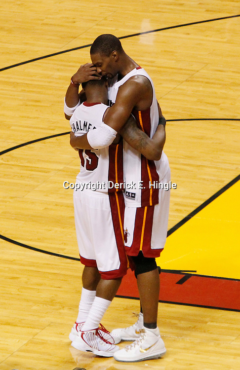 Jun 19, 2012; Miami, FL, USA; Miami Heat power forward Chris Bosh (1) hugs point guard Mario Chalmers (15) during the fourth quarter in game four in the 2012 NBA Finals against the Oklahoma City Thunder at the American Airlines Arena. Miami won 104-98. Mandatory Credit: Derick E. Hingle-US PRESSWIRE