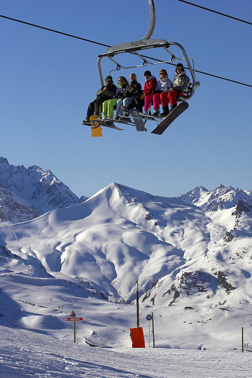 Editorial image. A group of skiers and snowboarders on a six man chairlift in Serre Chevalier, France