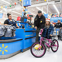 """Cibola County Sheriff Tony Mace helps Krysta McCracken, 8, from Laguna check out at Walmart,  Wednesday, Dec. 19 during their annual """"Shop with a Cop""""  event in Grants. 35 kids from Cibola County participated in the event which included a $250 gift card to spend at Walmart, lunch and a carnival at Knights of Columbus."""