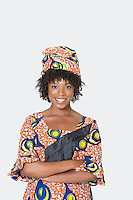 Portrait of young woman in African print attire standing arms crossed over gray background