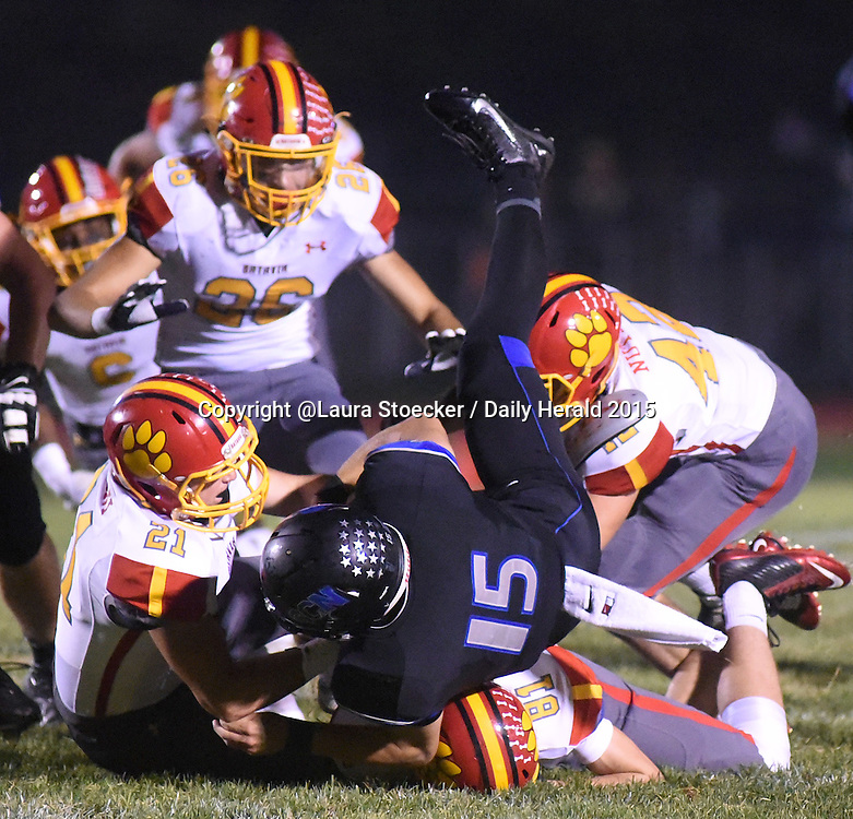 Laura Stoecker/lstoecker@dailyherald.com<br /> St. Charles North's Zach Mettetal (15) is taken down by Batavia's Connor Oroni (21), Jay Hunt (81) and Derek Nutley (42) in the first quarter Friday.