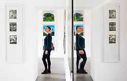 Yorkshire Sculpture Park (YSP) employee Kerry Chase is distorted as she is reflected in the glass of a picture frame at the YSP unveiling of their new Common Ground exhibition at the YSP in West Bretton, West Yorkshire.