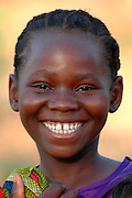 A girl from the village outside the South Luangwa National Park smiles at the camera..Mfuwe, Zambia, Africa.© Demelza Cloke