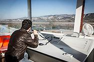 Pisticci Scalo, Basilicata, Italia 27/01/2016 <br /> Dirigente della Winfly al lavoro nella torre di controllo dell'aviosuperficie &quot;E.Mattei&quot;, vicino Matera.<br /> <br /> La struttura venne realizzata negli anni '60, durante l'industrializzazione della val Basento, su iniziativa di Enrico Mattei, per una sua personale maggiore rapidit&agrave; di spostamento tra i siti ENI.<br /> <br /> Inutilizzata per molto tempo. Il 22 maggio 2014 &egrave; stata affidata dal CSI (consorzio per lo sviluppo industriale) di Matera la gestione della stessa aviosuperficie alla societ&agrave; aerotaxi Winfly, che ha sede all'Aeroporto di Pontecagnano, vicino Salerno.<br /> <br /> Pisticci Scalo, Basilicata, Italy, 27/01/2016<br /> Manager of Winfly company working in the control tower of the airstrip &quot;E. Mattei&quot;, near Matera.<br /> <br /> The structure, a simple airstrip, was built in the 60s, during the industrialization of the Basento valley, on the initiative of Enrico Mattei, for a faster personal transfer between ENI company sites.<br /> <br /> Unused for a long time. On the 22nd May 2014 the CSI (Consortium for Industrial Development) of Matera entrusted the management of the airfield to the air taxi Winfly company, based in the Airport of Pontecagnano near Salerno.