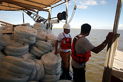 21 August 2010. Bay Jimmy, south Louisiana. <br /> Sub contractors, working for contractors working for BP check, replace, remove and deploy absorbent oil boom as the worst environmental disaster in US history continues to unfold in south Louisiana. Bay Jimmy received another recent coating of oil despite government and BP efforts to persuade the public otherwise. The sub contractors were ordered over the radio 'Do not talk to journalists.' The culture of fear remains whereby any contractor speaking to the media fears he may lose his job.<br /> Photo credit; Charlie Varley/varleypix.com