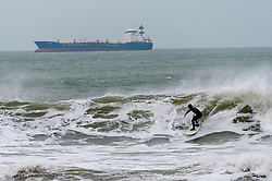 © Licensed to London News Pictures. 02/02/2017. Broad Haven, Pembrokeshire, Wales, UK. With a strong offshore wind, surfers enjoy clean waves at Broadhaven whilst tankers wait to dock at Milford Haven. The swell size is forecast to increase peaking around midnight tonight. BeachStrong winds and rain hit the Pembrokeshire coastline in Wales, UK. Photo credit: Graham M. Lawrence/LNP