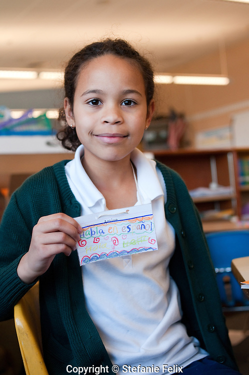 Spanish immersion 2nd grade student proudly shows the nametag she made and wears that says she speaks Spanish