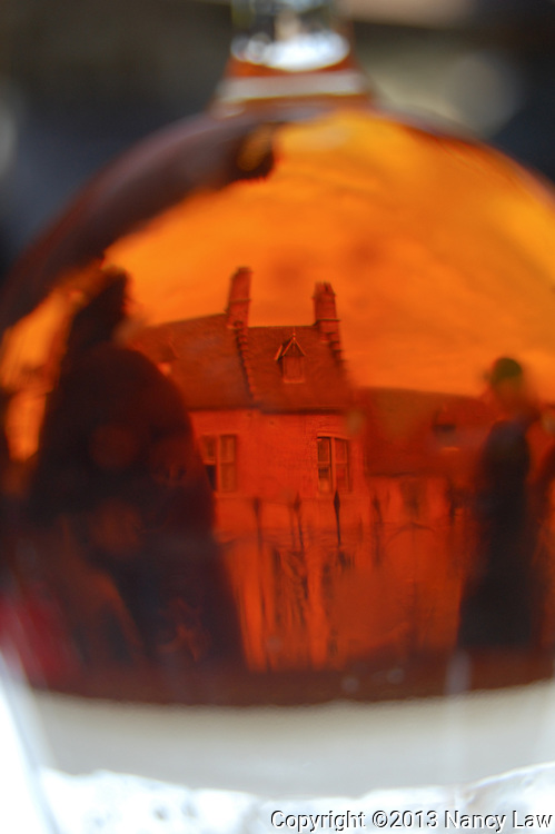Amber scene captured through a glass of Palm Ale in Bruges Begium. The old buildings and passersby produce a ghostly, haunting quality. The photo had to be flipped upside down due to the refraction from shooting through liquid.