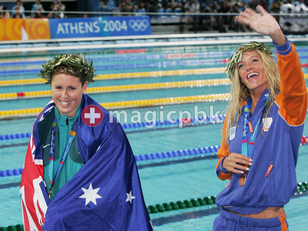 Australian swimmer Petria Thomas, (L) presents her gold medal, while Dutch Inge de Bruijn smiles with bronze, after their women's 100m butterfly final at the Athens Olympic Aquatic Centre Sunday 15 August 2004.           (Photo by Patrick B. Kraemer / MAGICPBK)