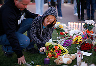 A young girl and her father lights a candle at a memorial outside the hospital where victims of yesterdays shootings are recovering in Tucson, Arizona January 9, 2011.  REUTERS/Rick Wilking (UNITED STATES)