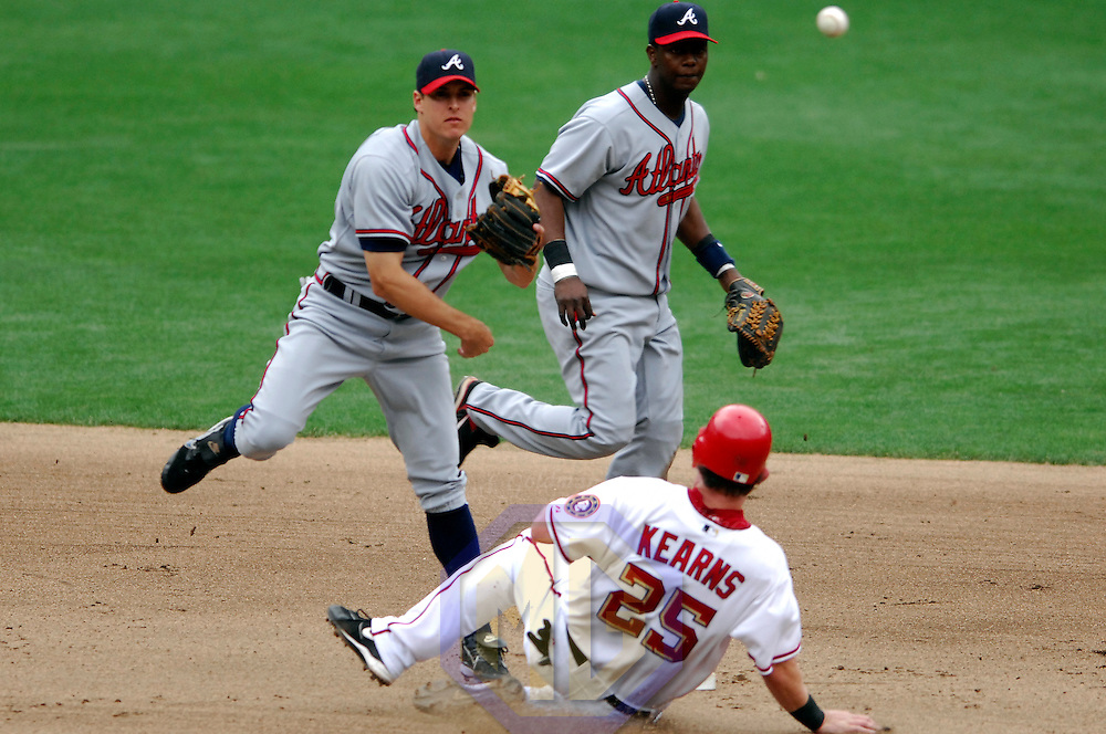 17 May 2006:   Atlanta Braves second baseman Kelly Johnson (L) completes a double play to end the 7th inning as shortstop Edgar Renteria (C) watches, on a ball hit by Washington Nationals first baseman Tony Batista as right fielder Austin Kearns (25) slides into second base. The Nationals defeated the Braves 4-3 at RFK Stadium in Washington, D.C.