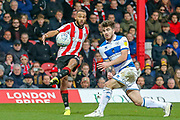 Brentford forward Bryan Mbeumo (19) passes, Queens Park Rangers forward Ryan Manning (14), during the EFL Sky Bet Championship match between Brentford and Queens Park Rangers at Griffin Park, London, England on 11 January 2020.