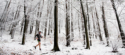 © Licensed to London News Pictures. 27/12/2017. Dorking, UK. A runner braves the snow showers and low temperatures to run through the forest on Leith Hill. Photo credit: Peter Macdiarmid/LNP