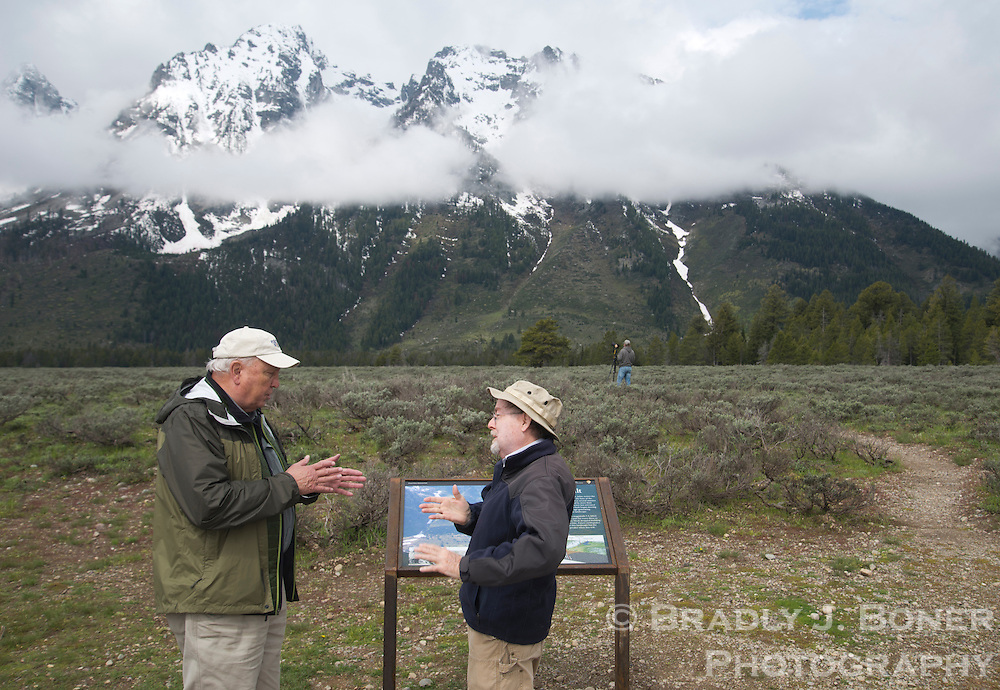 Dr. Robert Smith, emeritus professor of geophysics at the University of Utah, visits with Dr. Richard Kyle, geology professor at the University of Texas at Austin late last month at a turnout in Grand Teton National Park where the scarp face of the Teton Fault is visible at the base of the Teton Range.