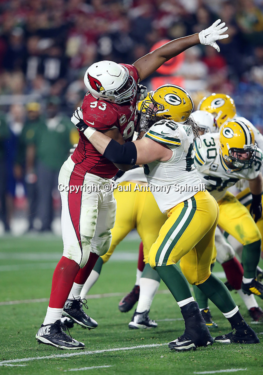 Arizona Cardinals defensive end Calais Campbell (93) reaches up with his outstretched arm and hand as he tries to knock down a pass while being blocked by Green Bay Packers tackle David Bakhtiari (69) during the NFL NFC Divisional round playoff football game against the Green Bay Packers on Saturday, Jan. 16, 2016 in Glendale, Ariz. The Cardinals won the game in overtime 26-20. (©Paul Anthony Spinelli)