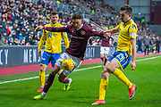 Sean Clare (#8) of Heart of Midlothian FC takes on Callum Booth (#24) of St Johnstone FC during the Ladbrokes Scottish Premiership match between Heart of Midlothian FC and St Johnstone FC at Tynecastle Park, Edinburgh, Scotland on 14 December 2019.