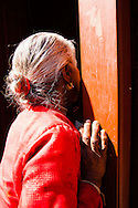 An elderly woman peers inside a store with the sun shining on her red blouse, in a small village called, Bungamati, just south of Kathmandu,Nepal.
