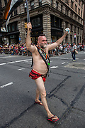 "New York, NY - 25 June 2017. New York City Heritage of Pride March filled Fifth Avenue for hours with groups from the LGBT community and it's supporters. A man dressed minimally, with a banner declaring him ""Mr. Stonewall Bear."""