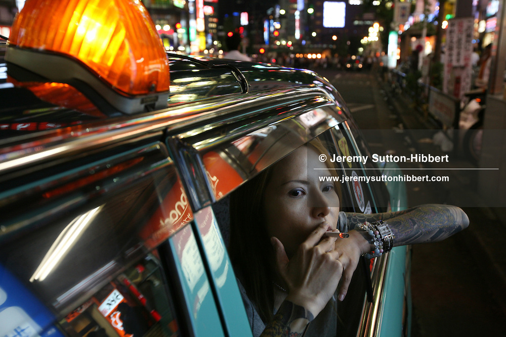 Shoko Tendo sits smoking in a taxi in the red light district of Kabukicho (where she used to work as a 'hostess' in a bar') , in Tokyo, Japan, Saturday, Sept. 1st, 2007. Shoko Tendo, daughter of Yakuza boss Hiroyasu Tendo (now deceased) has written an autobiographical book - 'Yakuza Moon',  describing her life growing up with a Yakuza criminal boss for a father, of her addiction to drugs, and the failed, and often violent sexual relationships she had with men. Shoko Tendo has a body covered in Yakuza style tattoos, including a large depiction of the Muromachi-period courtesan Jigoku Dayu (with a dagger clenched in her teeth), on her back. Shoko Tendo now lives in Tokyo with her 2 year old daughter Komachi.