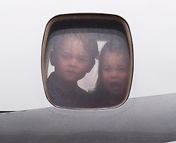 Prince George and Princess Charlotte look out of the plane window as they arrive with the Duke and Duchess of Cambridge at Warsaw's Chopin Airport for the start of their five-day tour of Poland and Germany.