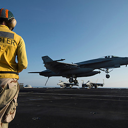 USS John C Stennis CVN-74 Aircraft Carrier.Pic Shows Lt Jordan Voss a shooter on the carrier watching as F-18 Super Hornets come in to land after missions