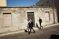 "PERDASDEFOGU, SARDINIA, ITALY - 30 JUNE 2013: (L-R) Stefano Lai, 27 (here together with his girlfriend), and his cousing Alberto Lai, 19, walk walk towards the church for the the mass celebrating their grandmother Claudina Melis' 100th birthday in Perdasdefogu, Italy, on June 30th 2013. Stefano Lai is now doing a post-doctoral fellowship in biomedical engineering at the prestigious Scuola Sant'Anna in Pisa. He would like to stay in Sardinia, or even in Italy, but doesn't have his hopes up. Alberto Lai lives and studies in Perdasdefogu.<br /> <br /> Last year, the Melis family entered the Guinness Book of World Records for having the highest combined age of any nine living siblings on earth — today more than 825 years. The youngest sibling, Mafalda – the ""little one"" – is 79 years old.<br /> <br /> The Melis siblings were all born in Perdasdefogu to Francesco Melis and Eleonora Mameli, who had a general store. Consolata, 106, is the oldest, then Claudia, 100; Maria, 98; Antonino, 94; Concetta, 92; Adolfo, 90; Vitalio, 87; Fida Vitalia, 81; and Mafalda, the baby at 79. Their descendants now account for about a third of the village."