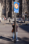 Europe, Germany, Cologne, woman behind a pole of a street sign photographs the Cologne cathedral...Europa, Deutschland, Koeln, Frau hinter einem Strassenschild fotografiert den Dom.