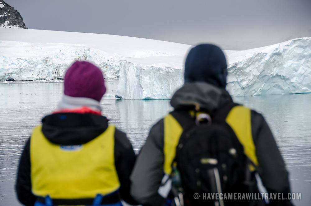 Passengers ready in their life vests admire the view of the landscape while waiting to board Zodiac inflatable boats to go ashore at Cuverville Island on the western side of the Antarctic Peninsula.