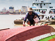 "17 JUNE 2013 - YANGON, MYANMAR:    A Burmese boat taxi operator paints his boat near the dock of the Yangon-Dala Ferry on the Dala side of the river. Yangon is in the background. The ferry to Dala opposite Yangon on the Yangon River is the main form of transportation across the river. Every day the ferry moves tens of thousands of people across the river. Many working class Burmese live in Dala and work in Yangon. The ferry is also popular with tourists who want to experience the ""real"" Myanmar. The rides takes about 15 minutes. Burmese pay about the equivalent of .06¢ US for a ticket.  Foreigners pay about the equivalent of about $4.50 US for the same ticket.   PHOTO BY JACK KURTZ"