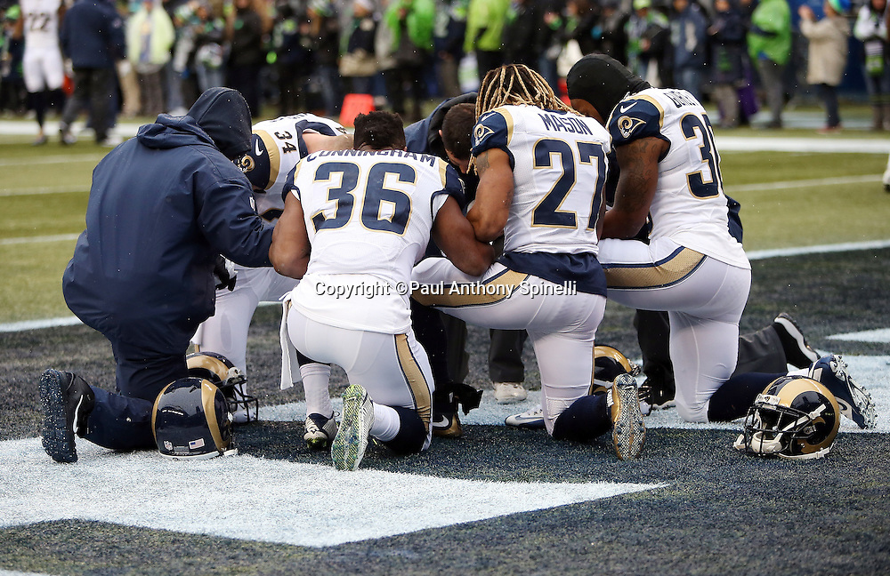 A group of St. Louis Rams kneel and take a group moment before the 2015 NFL week 16 regular season football game against the Seattle Seahawks on Sunday, Dec. 27, 2015 in Seattle. The Rams won the game 23-17. (©Paul Anthony Spinelli)