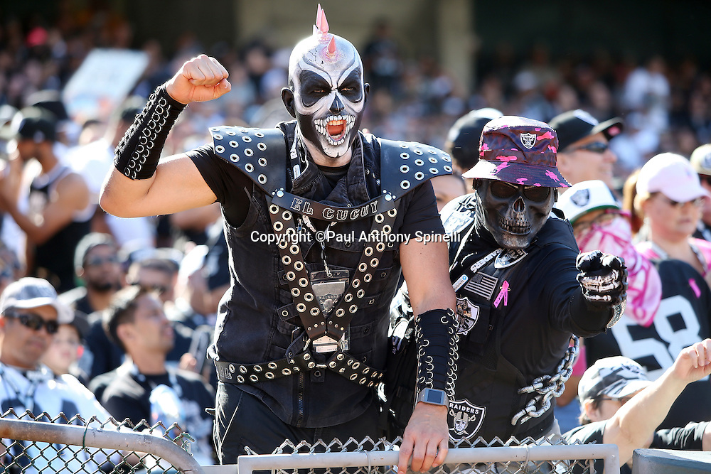An Oakland Raiders fan with a spiked and shaved head, black costume, and scary looking face paint cheers for the team next to a similarly costumed fan during the Oakland Raiders 2015 NFL week 5 regular season football game against the Denver Broncos on Sunday, Oct. 11, 2015 in Oakland, Calif. The Broncos won the game 16-10. (©Paul Anthony Spinelli)