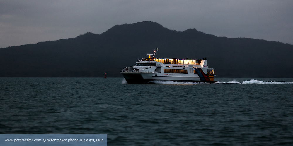 Fullers ferry Starflyte passing Rangitoto Island at night. Waitemata Harbour,  Hauraki Gulf, Auckland.
