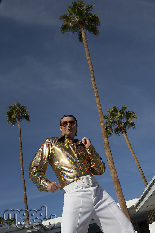 Low angle view of middle-aged man impersonating Elvis Presley
