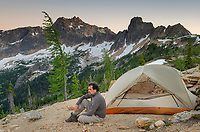 Adult male sitting next to backpacking tent and gazing at view on ridge above Cutthroat Pass, near Pacific Crest trail. North Cascades Washington