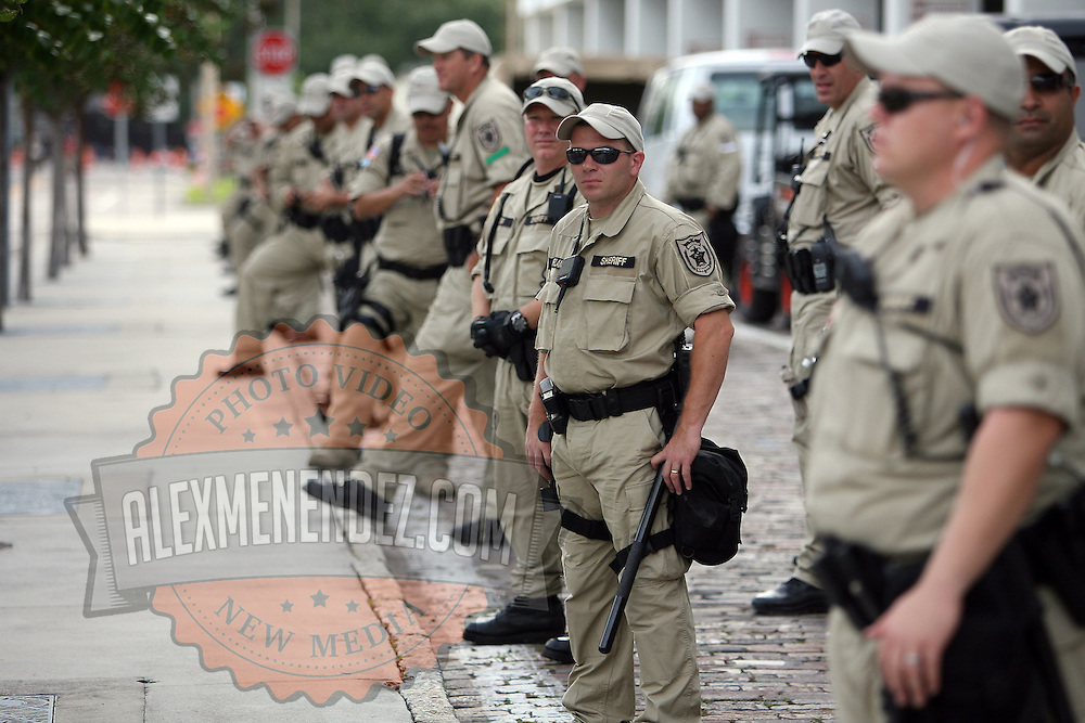 Police officers watch as a protest parade approaches them during the Republican National Convention in Tampa, Fla. on Wednesday, August 29, 2012. (AP Photo/Alex Menendez)