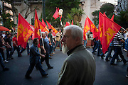 A supporter of the Greek communist party (KKE) watches the parade of flags in Athens, Greece. Image © Angelos Giotopoulos/Falcon Photo Agency