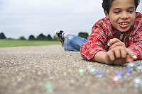 Boy (7-9) playing marbles lying in playground