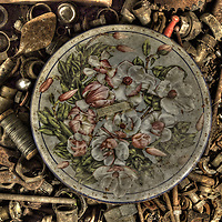 An old tin with a decorative floral design in a box of old nuts and bolts