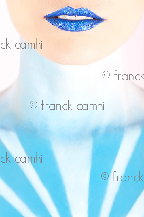 Detail shot of an artistic woman painted with blue representing the sky isolated on pink background