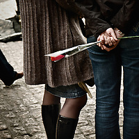 A man holds a rose for his girlfriend in the street