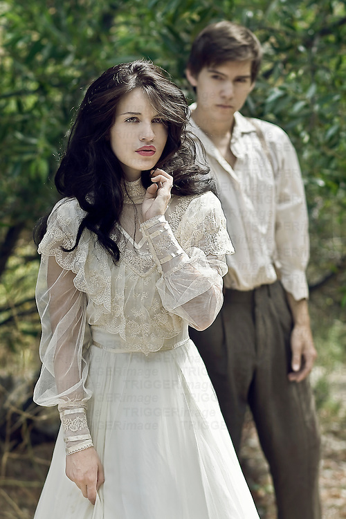 A young woman walking away from a young man dressed in period costume