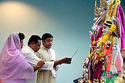 Nederland, Wijchen, 16-1-2006..Ceremonie ter inwijding van de hindoetempel, de Shree Raam Mandir, die deel uitmaakt van een nieuw cultureel, centrum, het grootste van het land...de De inwijding bestaat uit het reinigen van de moerties, de kleurrijke beelden, teneinde er leven in te brengen. Hierna krijgen ze kleren en bloemslingers aangedaan. Door de lengte van de ceremonie voor elk beeld duurt de inwijding vier dagen. Gebedshuis, hindoe, hindu, hindoestanen, hindoepriester, oosterse religie, godsdienst, geloof, hindoeisme, tempel, kultuur, multicultureel...Foto: Flip Franssen