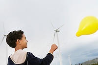 Boy (7-9) playing with balloon at wind farm