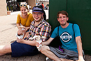 Three Artscape attendees pose for a photo with a festival staple, a turkey leg, in Baltimore, MD on Sunday, July 21, 2013.