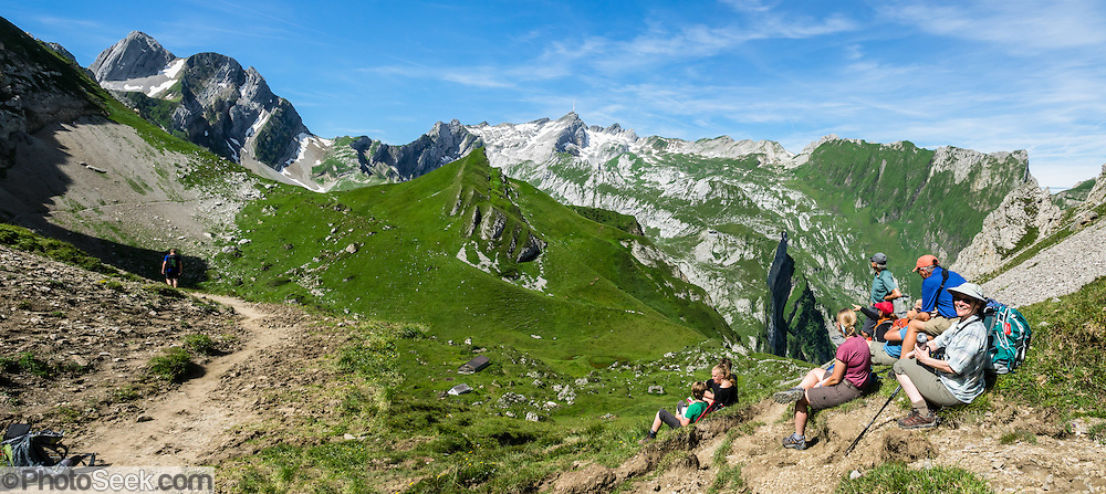 Hikers at Bötzel pass contemplate the distant peak of Santis, in Switzerland, Europe. Shared by three cantons, Säntis (2502 m/8209 ft) is the highest mountain in the Alpstein massif of northeastern Switzerland, and highest of the Appenzell Alps, which rise between Lake Walen and Lake Constance. Accessible via cable car or spectacular trails, Säntis provides a spectacular view across six countries: Switzerland, Germany, Austria, Liechtenstein, France and Italy. This image was stitched from multiple overlapping photos.