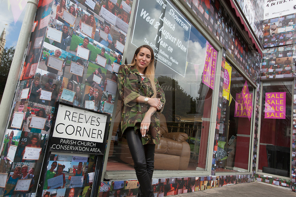 """© licensed to London News Pictures. London, UK 06/08/2012. British singer-songwriter Delilah posing outside the House of Reeves furniture store which was burnt down in last year's riots. The shop has been covered in 4000 images of young people with positive messages on August 6, 2012 in Croydon. The youth volunteering charity """"vInspired"""" are marking the one year anniversary of the riots in Croydon by displaying thousands of images of young Britons holding up positive messages about themselves on the House of Reeves furniture store which was destroyed in last year's violence. British singer-songwriter Delilah is one of the supporters of the volunteering charity """"vInspired"""". Photo credit: Tolga Akmen/LNP"""