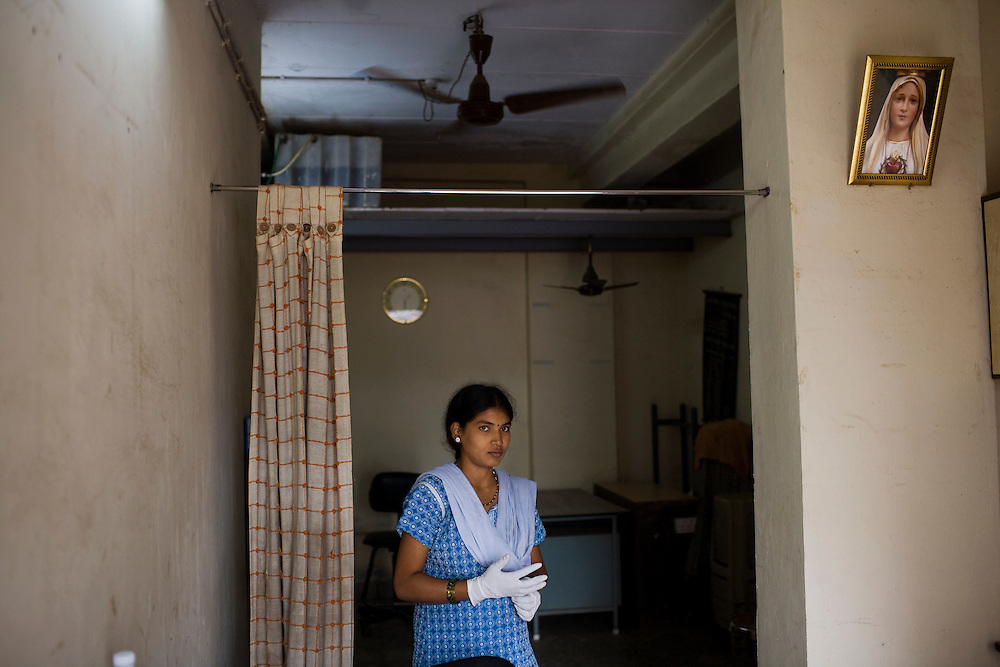 Rajeshree Bamsode, a lab worker with a local NGO, stands in a small makeshift lab where she examines patient sputum samples to determine if they have active TB.